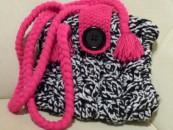 Handtasche mit Zopfmuster, großem Knopf und pinken Henkeln